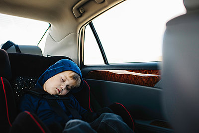 Young boy sleeping in back seat of car - p924m1224656 by Jennifer van Son
