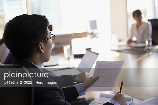 Male lawyer with paperwork listening in conference room meeting