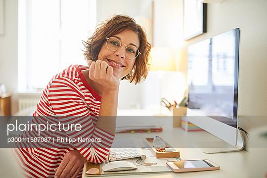 Portrait of content mature woman sitting at desk at home - p300m1587087 von Philipp Nemenz