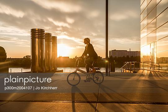 Senior woman riding city bike at the riverside at sunset - p300m2004107 von Jo Kirchherr