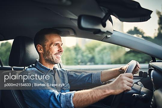 Handsome man driving a car - p300m2154633 by Bartek Szewczyk