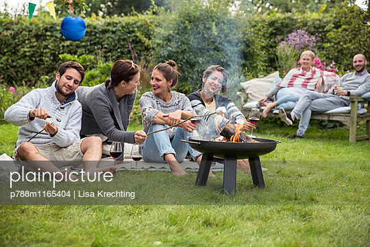 Friends roasting marshmallows at garden party - p788m1165404 by Lisa Krechting