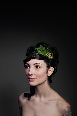 Woman wearing leaves in hair against black background - p1166m1163790 by Cavan Images