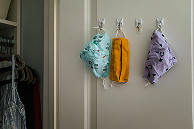 three cloth masks hanging on hooks in closet - p1166m2212675 by Cavan Images