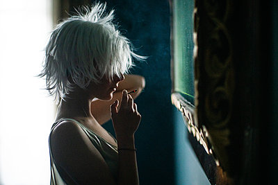 Smoking woman with white hair takes a look in the mirror - p1321m2223400 by Gordon Spooner