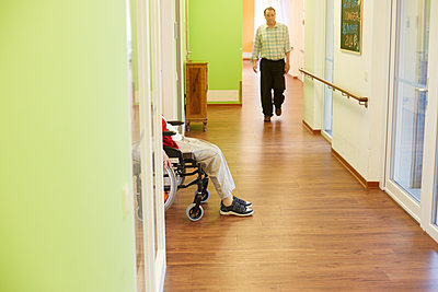 Age demented senior man walking on corridor in a nursing home - p300m2219186 by Heinz Linke