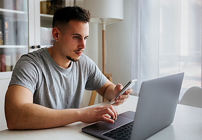 Handsome male entrepreneur with smart phone using laptop on table at home office - p300m2266931 by Marco Govel