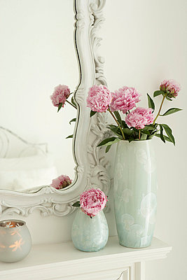 Pink Peonies in two vases beside ornate mirror frame - p3493221 by Jon Day