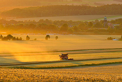 Landscape with harvesting machinery in field, Germany - p352m2120893 by Eddie Granlund