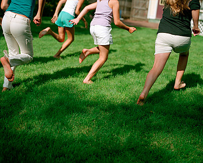 Detail of four girls running across lawn - p3720338 by James Godman