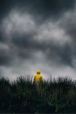 Figure in yellow anorak standing  in moorland under dark clouds - p597m2206411 by Tim Robinson