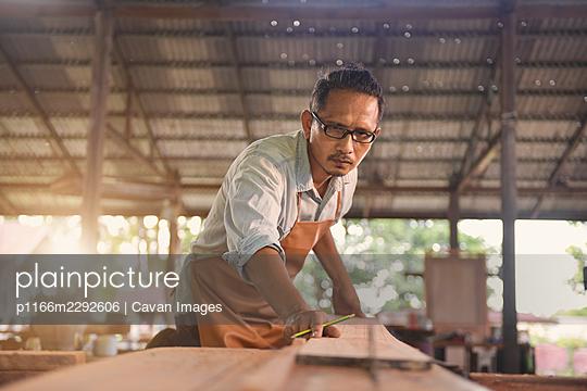 Carpenters using circular saw in workshop - p1166m2292606 by Cavan Images