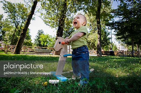 Portrait of baby girl playing with rocking horse on a lawn in a park. - p429m2190409 by Stefano Oppo