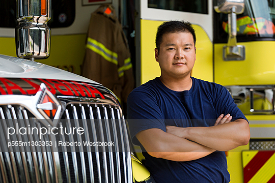 Serious Chinese fireman posing with fire truck