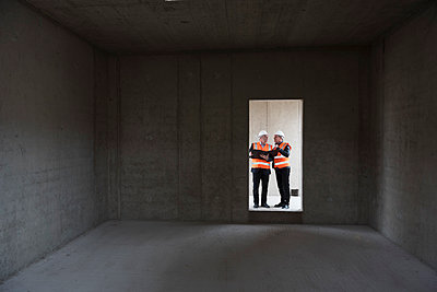Two men wearing safety vests talking in building under construction - p300m1460503 by Daniel Ingold