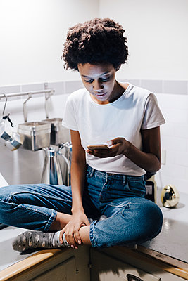 Young woman sitting on kitchen worktop, checking messages on smartphone - p300m1549786 by Giorgio Fochesato