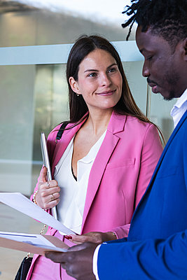 Female entrepreneur with laptop looking at coworker holding file - p300m2276183 by NOVELLIMAGE