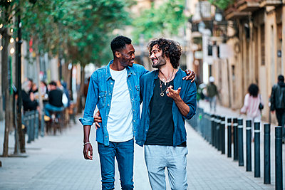 Gay man with arm around talking to friend while walking on footpath - p300m2287226 by Alvaro Gonzalez