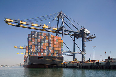 Container ship below cranes at a commercial dock - p30118156f by Michael Wells