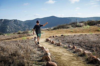 Boy stepping across row of footpath stones, Thousand Oaks, California USA - p429m1084515 by Ian Spanier