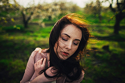 Wind blowing hair of pensive Caucasian woman - p555m1481993 by Kateryna Soroka