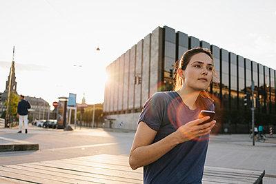 Junge Frau mit dem Smartphone unterwegs in der Stadt - p586m952008 von Kniel Synnatzschke
