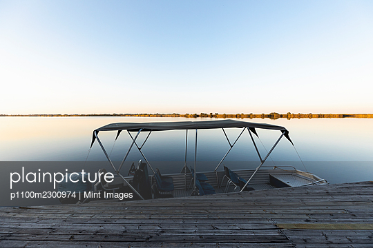 Boat moored at a jetty on the waters of the Okavango Delta at sunset, Botswana. - p1100m2300974 by Mint Images