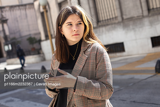 girl with a smartphone in her hands on a street in Buenos Aires - p1166m2232387 by Cavan Images