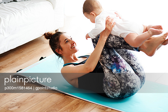 Mother and baby exercising on yoga mat at home - p300m1581464 von gpointstudio