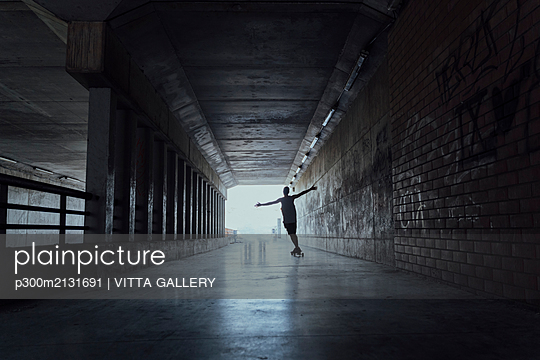 Silhouette of young man with longboard in a tunnel - p300m2131691 by VITTA GALLERY