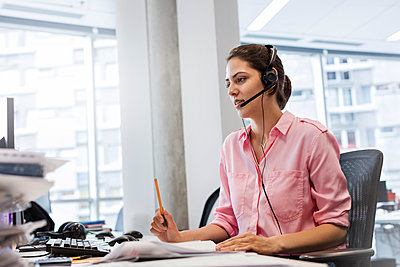 Businesswoman with hands-free device talking on telephone at office desk - p1023m1194324 by Rafal Rodzoch