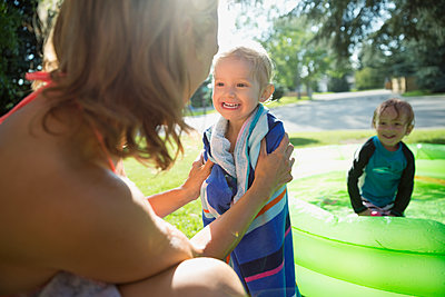 Mother wrapping cute daughter in towel next to wading pool in sunny backyard - p1192m1184006 by Hero Images
