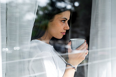 Young woman with cup of coffee behind windowpane - p300m2120063 by Giorgio Fochesato