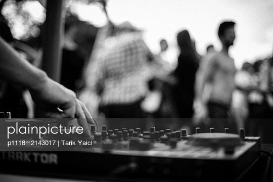 DJ legt Musik auf im Hintergrund tanzende Gruppe - p1118m2143017 von Tarik Yaici