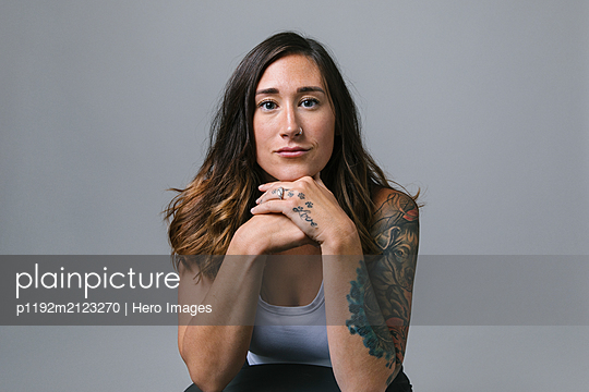 Portrait confident, strong young woman with tattoos and nose ring - p1192m2123270 by Hero Images