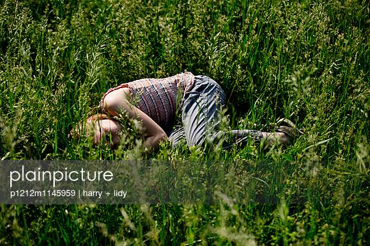 Mädchen liegt auf der Seite im Gras - p1212m1145959 von harry + lidy