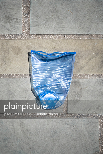 A blue tinted clear Polypropylene plastic disposable cup crushed on the ground - p1302m1590093 by Richard Nixon