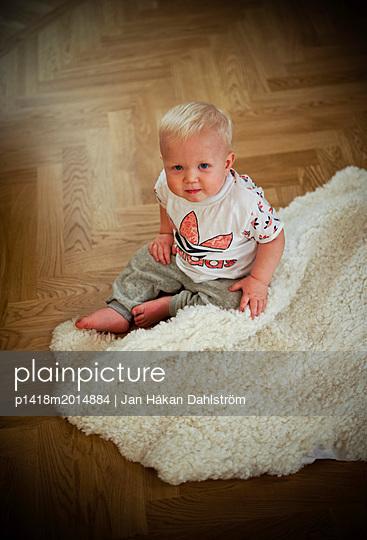 Kleiner Junge sitzt auf dem Fußboden neben einem Schaffell - p1418m2014884 von Jan Håkan Dahlström