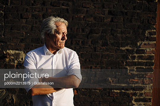 Man with arms crossed looking away while standing against brick wall - p300m2213975 by Gustafsson