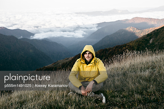 Caucasian man sitting in remote mountain landscape - p555m1491025 by Alexey Karamanov