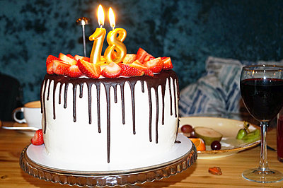 A birthday cake with burning candles is on the table - p1166m2280325 by Cavan Images
