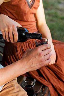 Paar beim Wein auf der runden Gartenbank - p1212m1159044 von harry + lidy