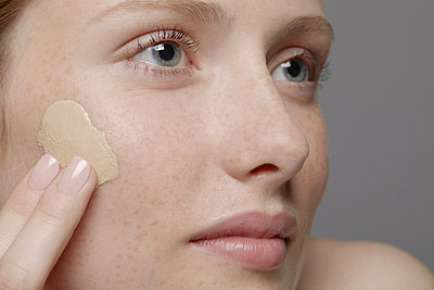 Close up of part of young woman's face, applying concealer - p924m805920f by Emma Kim