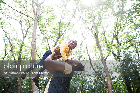 Playful carefree father lifting daughter below trees in sunny park - p1023m2238532 by Tom Merton