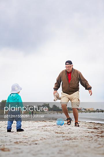 plainpicture - plainpicture p312m1558281 - Grandfather kicking ball on... - plainpicture/Johner