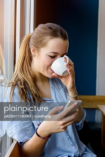 Young woman holding smartphone drinking coffee - p429m1118396f by suedhang photography