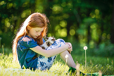 Young Girl Playing with Kitten in Outside - p1166m2146634 by Cavan Images