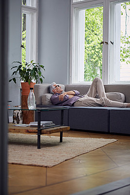 Mature man sleeping on couch at home - p300m2030208 by Rainer Berg