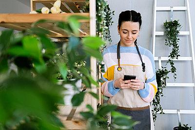 Young woman working in a gardening laboratory or plant shop - p300m2275369 von Giorgio Fochesato