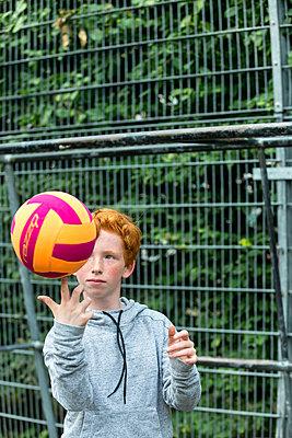 Rothaariges Mädchen balanciert Ball auf einem Finger - p427m1465575 von R. Mohr